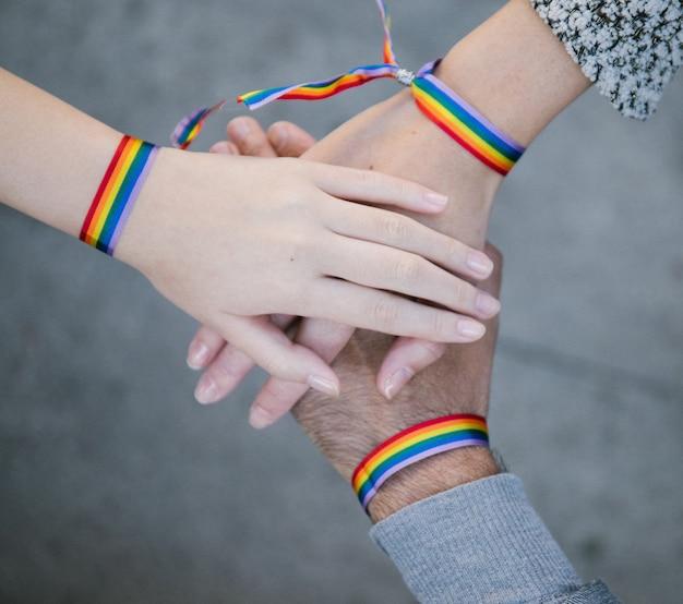 Pessoas homossexuais com pulseiras de arco-íris empilhando as mãos
