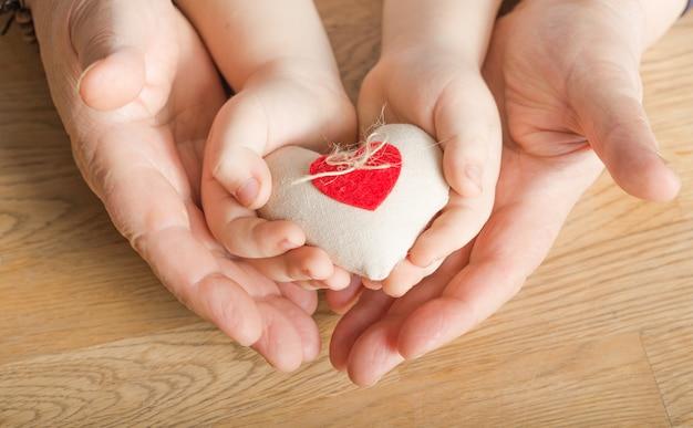 Pessoas, idade, família, amor e conceito de cuidados de saúde - close-up da mulher sênior e menino mãos segurando um coração vermelho sobre fundo de madeira
