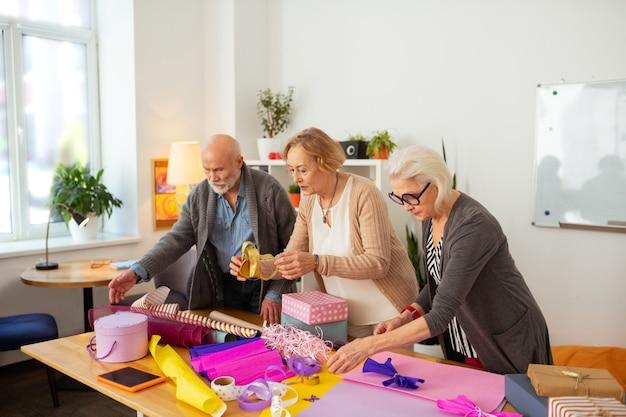 Pessoas idosas agradáveis olhando para o papel de embrulho enquanto se preparam para embrulhar presentes
