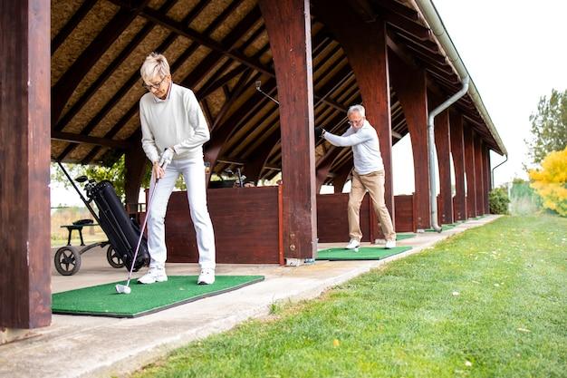 Pessoas idosas aproveitando a aposentadoria e praticando lances de longa distância no campo de golfe.