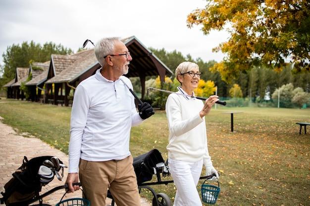 Pessoas idosas aproveitando a aposentadoria relaxando e jogando golfe.