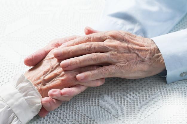 Pessoas idosas de mãos dadas. fechar-se.