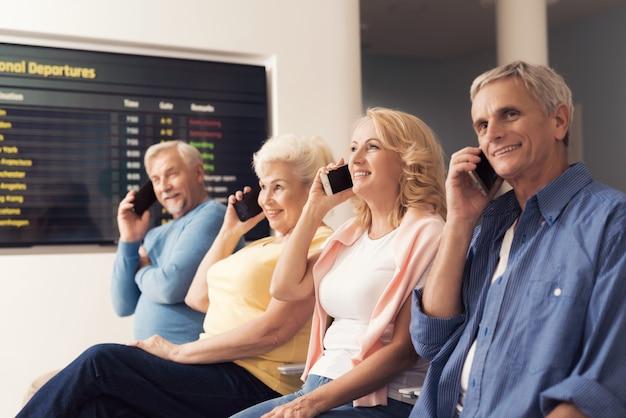 Pessoas idosas estão sentadas na sala de espera no aeroporto