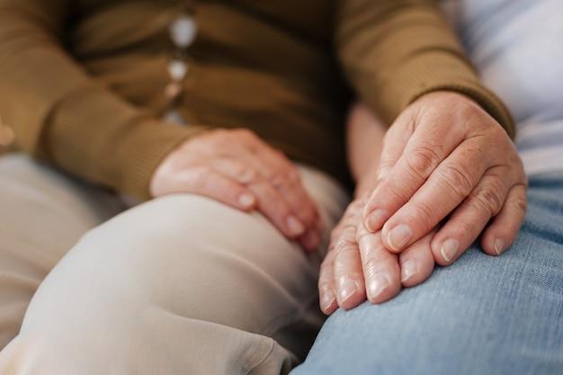 Pessoas idosas passando um tempo juntos e sentando-se lado a lado enquanto tocam as mãos