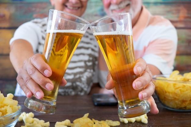 Pessoas idosas sorridentes sentadas no bar em uma mesa de madeira brindando com dois copos de cerveja e batatas fritas.