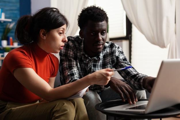 Pessoas inter-raciais olhando para laptop para pagar impostos