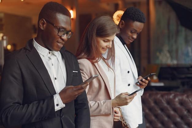 Pessoas internacionais em pé em um café com telefone móvel