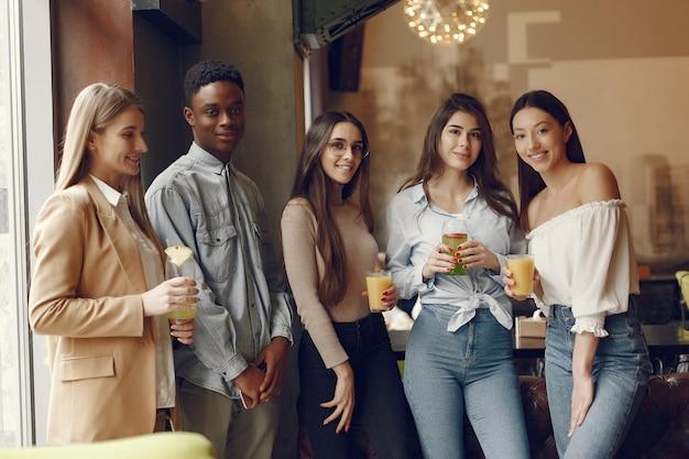 Pessoas internacionais em pé em um café e beber um coquetel