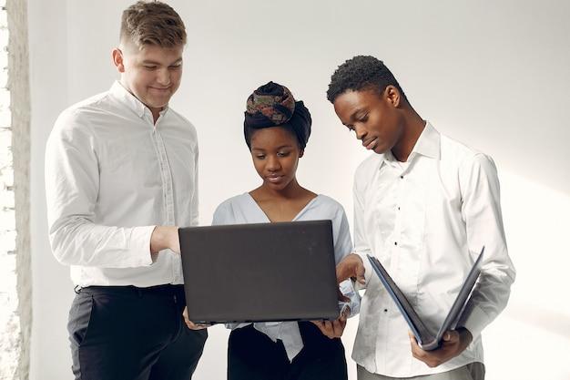 Pessoas internacionais em pé em uma parede branca com um laptop