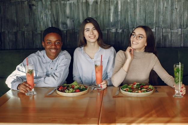 Pessoas internacionais sentados à mesa com saladas e cocktails