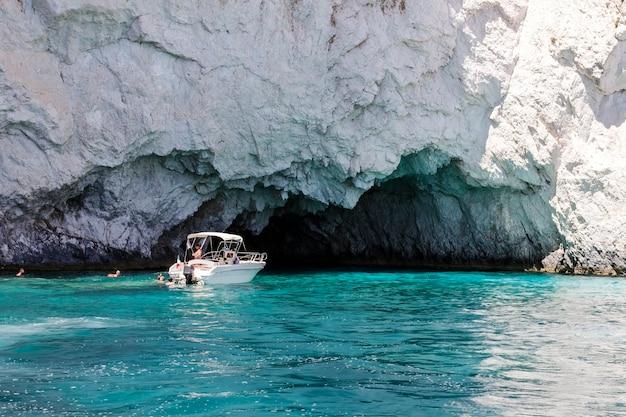 Pessoas irreconhecíveis nadando perto de um barco a motor perto das cavernas azuis na ilha de zakynthos, na grécia, na europa