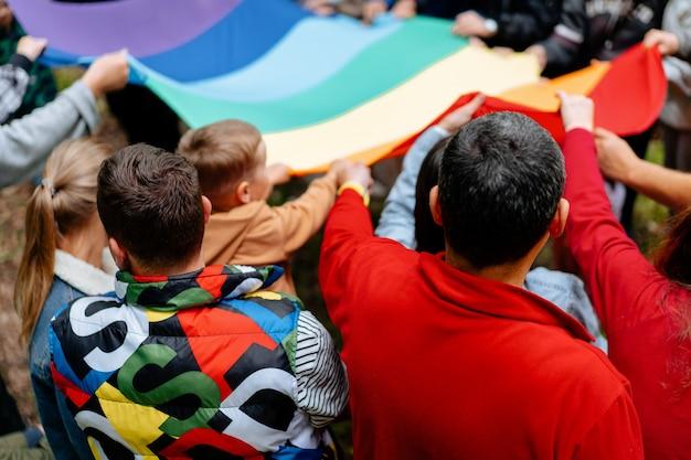 Pessoas irreconhecíveis segurando a bandeira do arco-íris lgbt comunidade do orgulho em um desfile conceito de igualdade certa