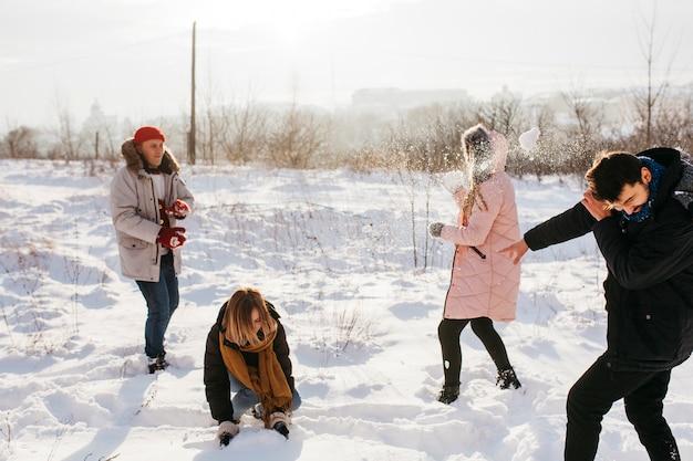 Pessoas jogando bolas de neve na floresta de inverno