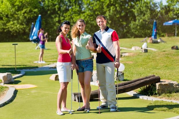 Pessoas jogando golfe em miniatura ao ar livre