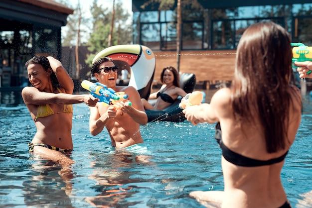 Pessoas jogando junto com pistolas de água coloridas