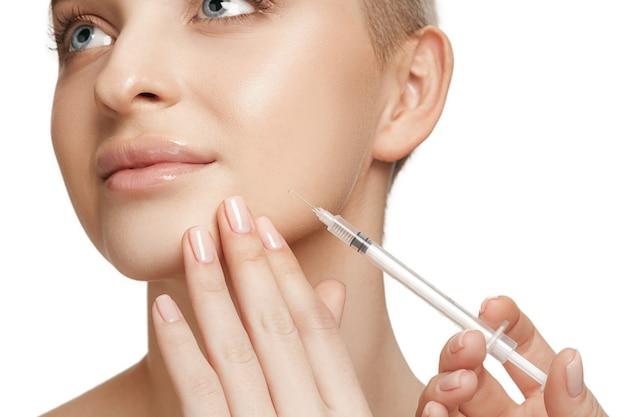 Pessoas, lábios, cosmetologia, cirurgia plástica e conceito de beleza - rosto e mão de mulher jovem e bonita com injeção de seringa