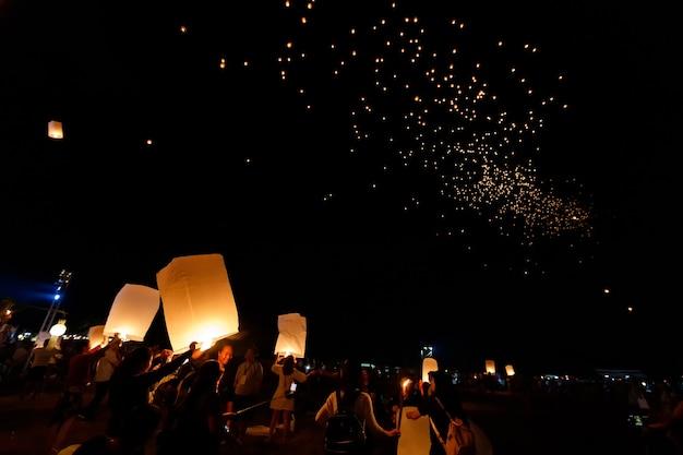 Pessoas lançando lanternas flutuantes no festival loi krathong