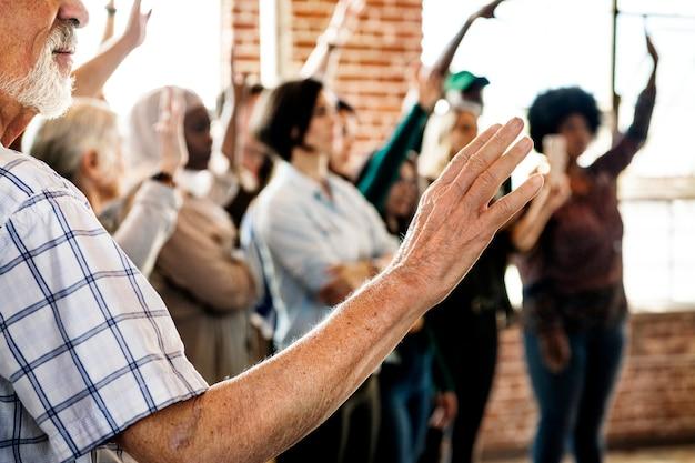 Pessoas levantando as mãos em um seminário