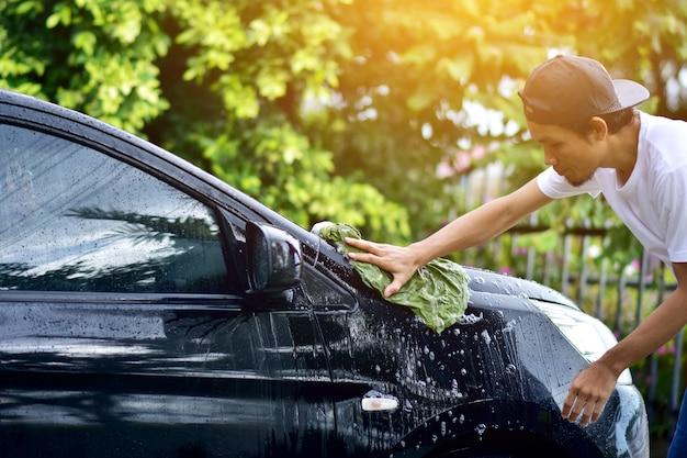 Pessoas limpando carro em casa luz solar