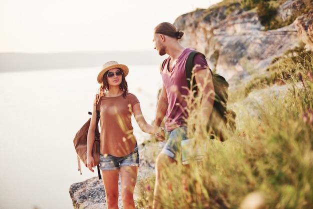 Pessoas lindas no fundo majestoso. o jovem casal decidiu passar as férias de forma ativa na beira de uma linda rocha com um lago ao fundo.