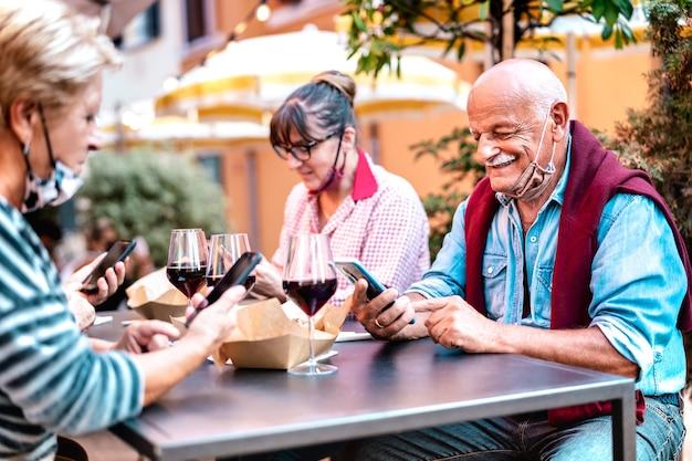 Pessoas maduras usando telefone celular inteligente com máscara facial aberta