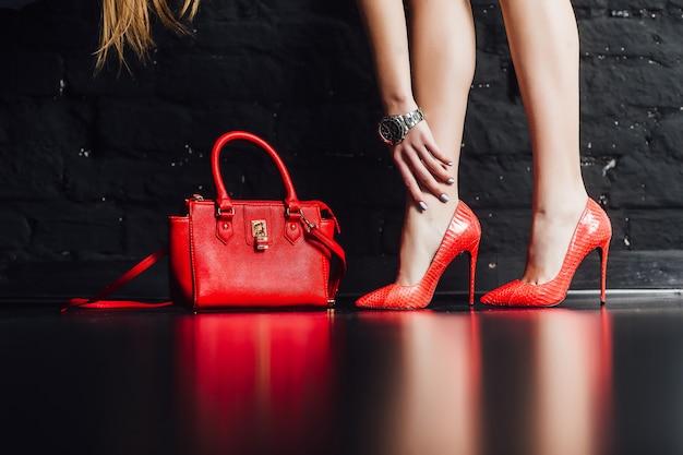 Pessoas, moda e calçados, close-up de pernas de mulher em sapatos de salto alto vermelhos