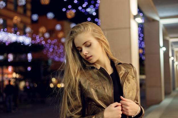 Pessoas, moda, estilo de vida e conceito de cor - mulher jovem e bonita sorrindo e posando à noite na rua da cidade contra a superfície do bokeh das luzes da noite