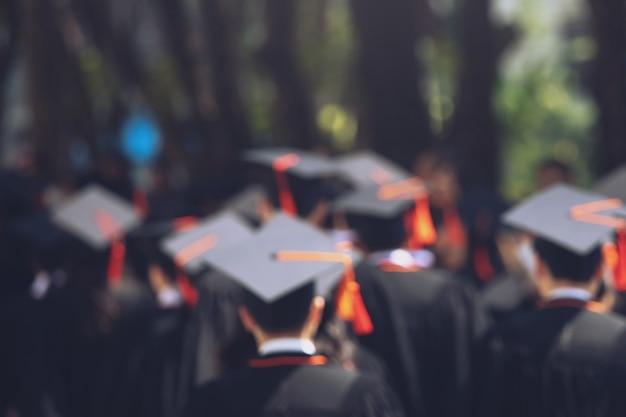 Pessoas mostram mão espera mostrar chapéu borlas azuis no fundo edifício da escola. foto do chapéu de formatura durante o conceito de diploma universitário de iniciação, conceito de aprendizagem de sucesso do aluno de educação de celebração
