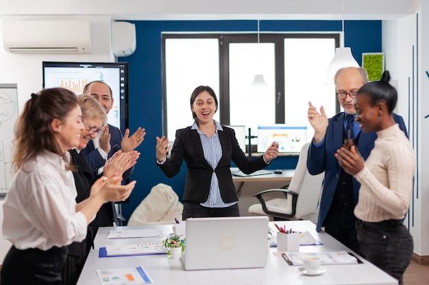 Pessoas motivadas da equipe de negócios diversificados batendo palmas e comemorando o sucesso na reunião corporativa