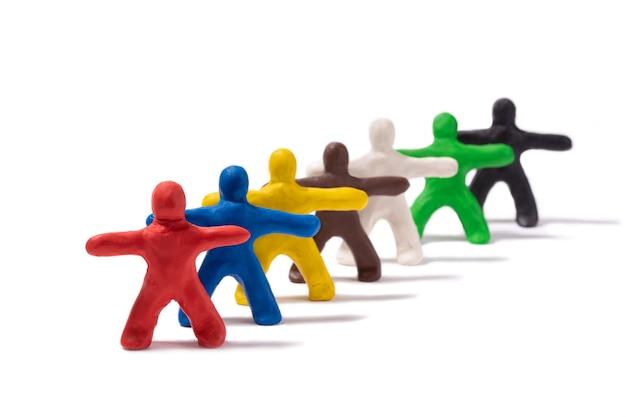Pessoas multicoloridas feitas de plasticina ficam atrás umas das outras em um fundo branco