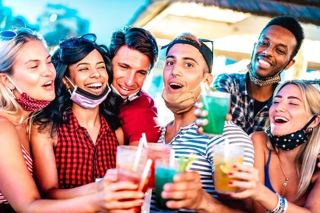 Pessoas multiculturais felizes brindando em bar noturno com máscaras abertas