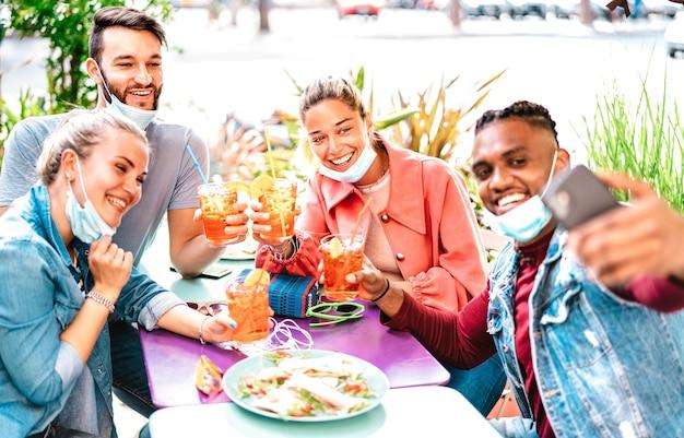 Pessoas multiculturais tirando selfie com máscaras abertas em um bar de coquetéis