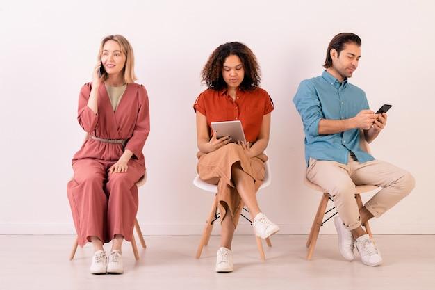 Pessoas multiétnicas modernas em roupas casuais, sentadas em cadeiras enfileiradas e usando gadgets o tempo todo para se comunicar