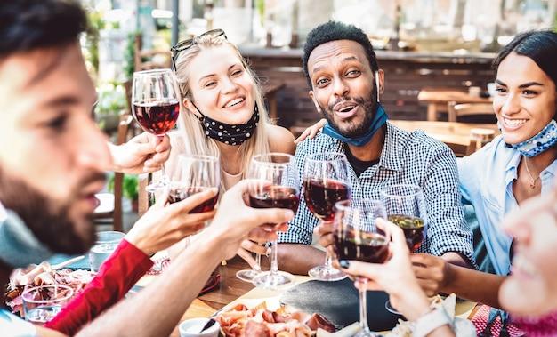 Pessoas multirraciais brindando vinho no jardim do restaurante usando máscara aberta