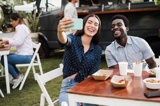Pessoas multirraciais se divertindo fazendo selfie com o celular em um restaurante food truck ao ar livre. foco no rosto do homem afro-americano