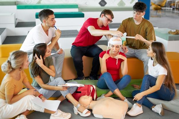 Pessoas na aula de primeiros socorros, aprendem a enfaixar a cabeça