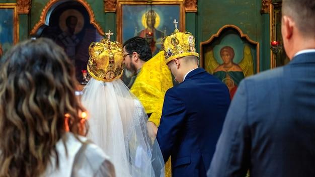 Pessoas na cerimônia de casamento, padre ortodoxo servindo em uma igreja