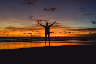 Pessoas na costa do oceano ao pôr do sol. homem salta contra o pano de fundo do sol poente