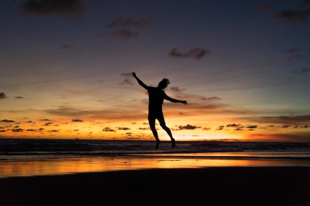Pessoas na costa do oceano ao pôr do sol. homem salta