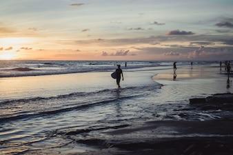 Pessoas na costa do oceano ao pôr do sol.