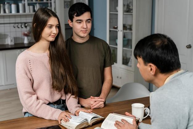 Pessoas na cozinha com bíblias