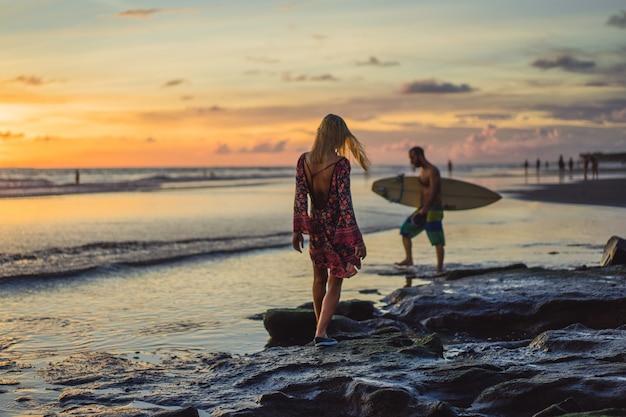 Pessoas na praia ao pôr do sol. a menina está saltando contra o pano de fundo do sol poente.