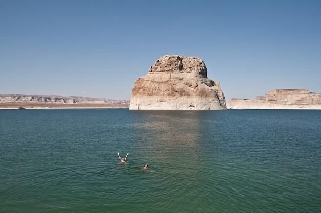 Pessoas nadando na água perto de uma grande pedra com um céu claro