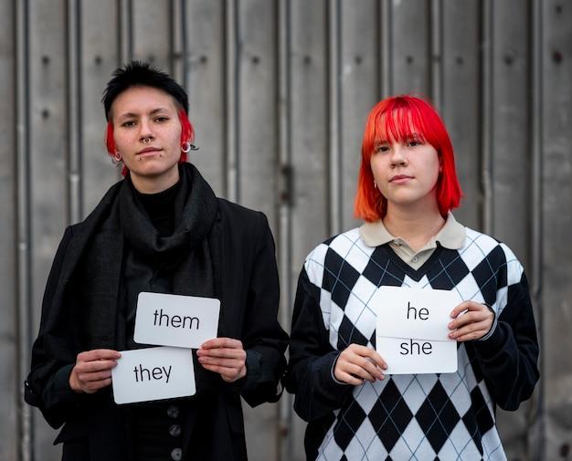Pessoas não binárias segurando cartas de pronomes