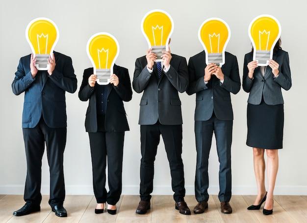 Pessoas negócio, segurando, lightbulb, ícones