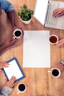 Pessoas negócio, usando, tecnologias, enquanto, segurar copos café, escrivaninha