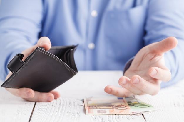 Pessoas, negócios, finanças e conceito de dinheiro - close-up de mãos de empresário segurando uma carteira aberta com dinheiro do euro