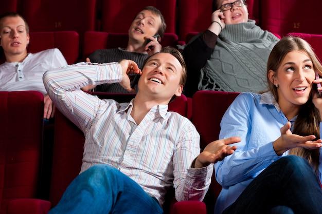 Pessoas no cinema com telefone móvel