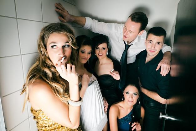 Pessoas no clube fumando no banheiro