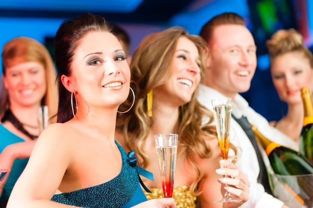 Pessoas no clube ou bar bebendo champanhe
